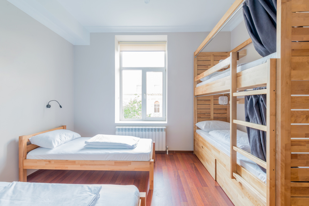 pokój w którym znajduje się łóżko piętrowe i dwa pojedyncze łóżka jest to pokój czteroosobowy w kolorze białym i oknem na wprost