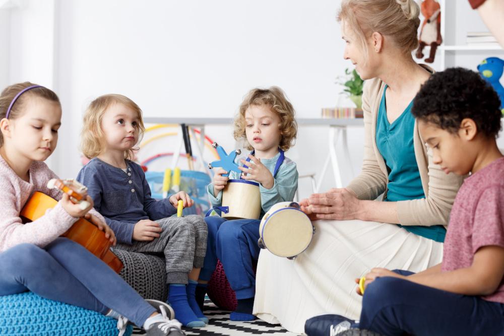 czworka dzieci spedzajacych czas w przedszkolu i grajacych na instrumentach
