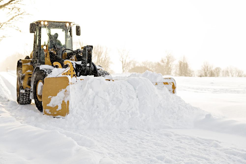 żółty traktor odśnieża drogę