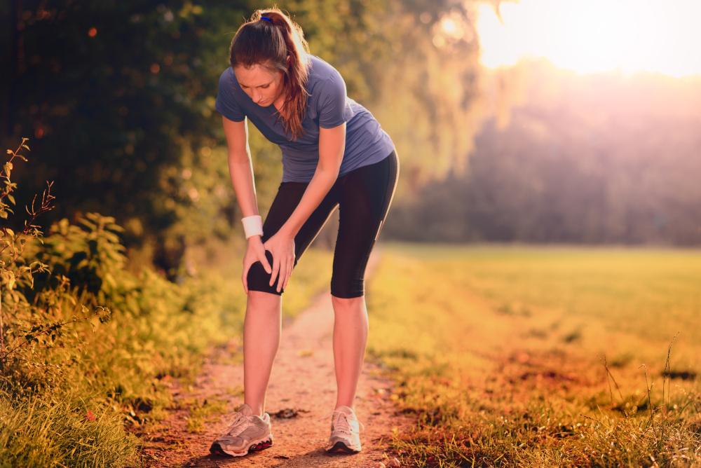 mloda kobieta biegnaca sciezka polna doznala urazu kolana