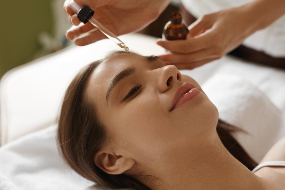 nakładanie pipetą olejku na twarz kobiety