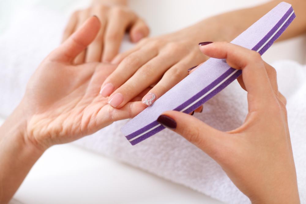 kosmetyczka piłująca kobiecie paznokcie u dłoni