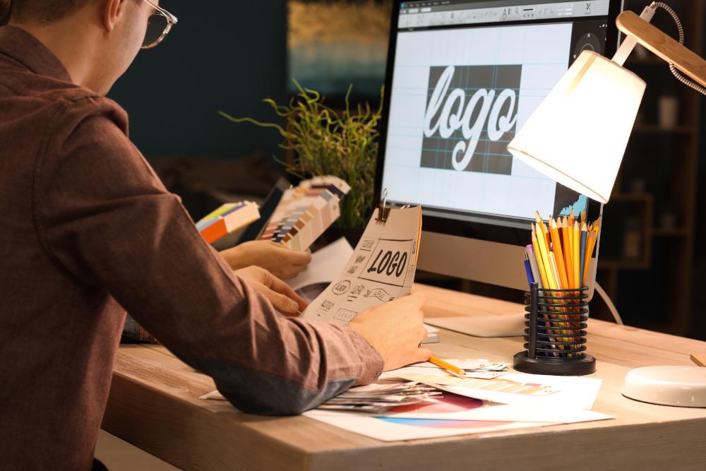 mężczyzna prjektujący logo reklamy na komputerze
