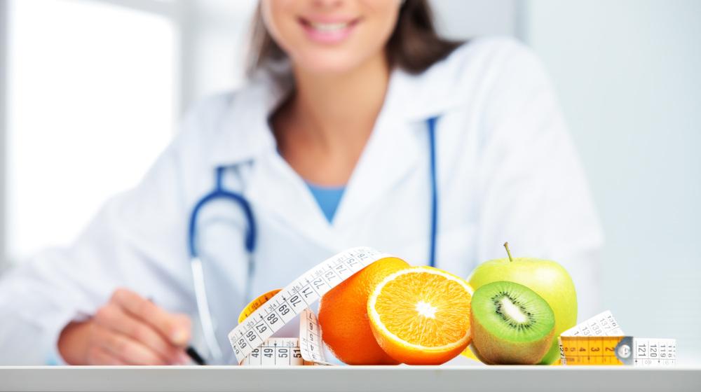 dietetyk która na biurku ma owoce i centymetr