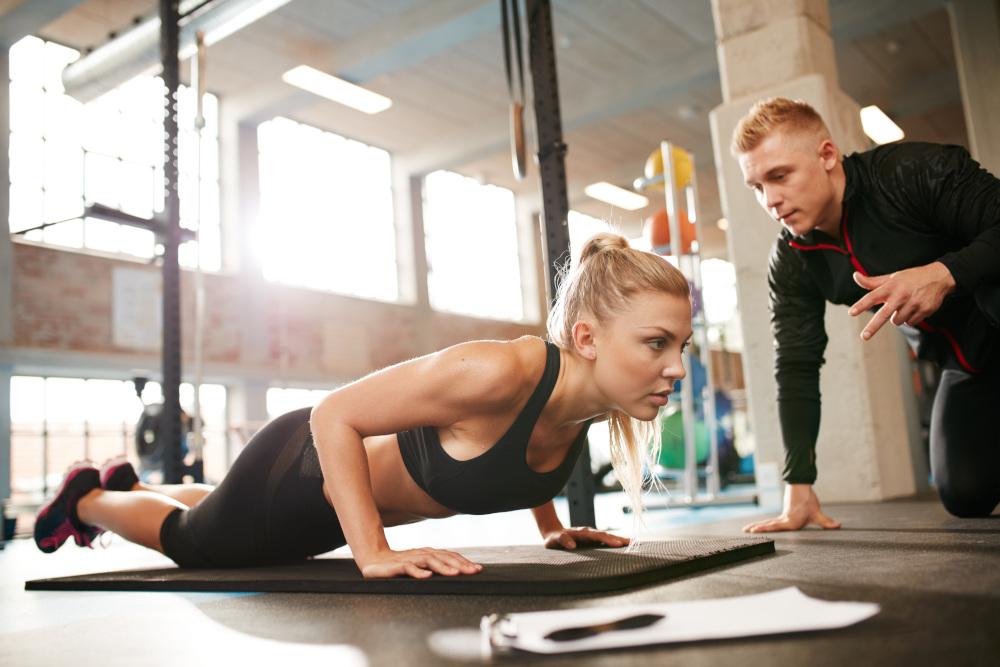 trener personalny z kobietą która wykonuje ćwiczenia
